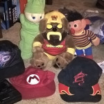 A Captain EO cap, Mario cap, an old baseball hat with fire on it that I wore for the entire year of 2001, a Hulk Hogan dog, Ernie, and a Glowworm.